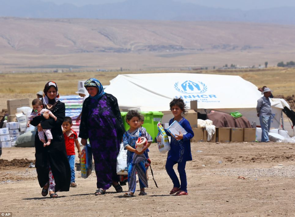 Iraqis who have fled fighting between security forces and al-Qaida inspired militants in their hometown of Tal Afar carry their belongings at Germawa camp for displaced Iraqis