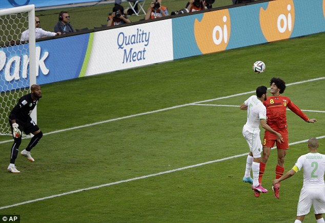 Bullet: Fellaini (right) jumps highest to head Belgium level against Algeria their 2-1 comeback victory