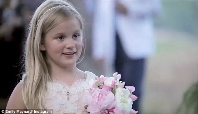Adorable: Emily's eight-year-old daughter Ricki held onto a petite bouquet of pink roses while wearing a lace dress