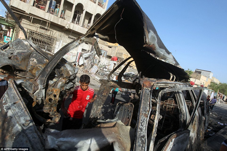 Carnage: A boy inspects the site of the car bomb which came amid a week-long militant offensive in which rebels have seized vast swathes of territory in northern Iraq