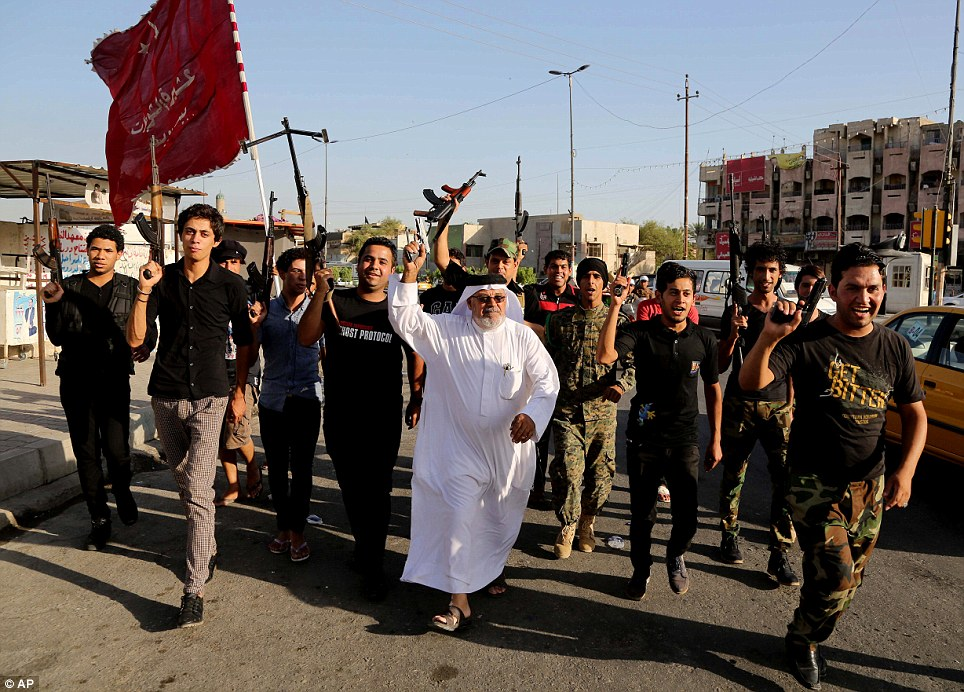 Resistance: Shi'ite tribal fighters raise their weapons and chant slogans against ISIS in Baghdad's Sadr City after authorities urged Iraqis to help counter the insurgency