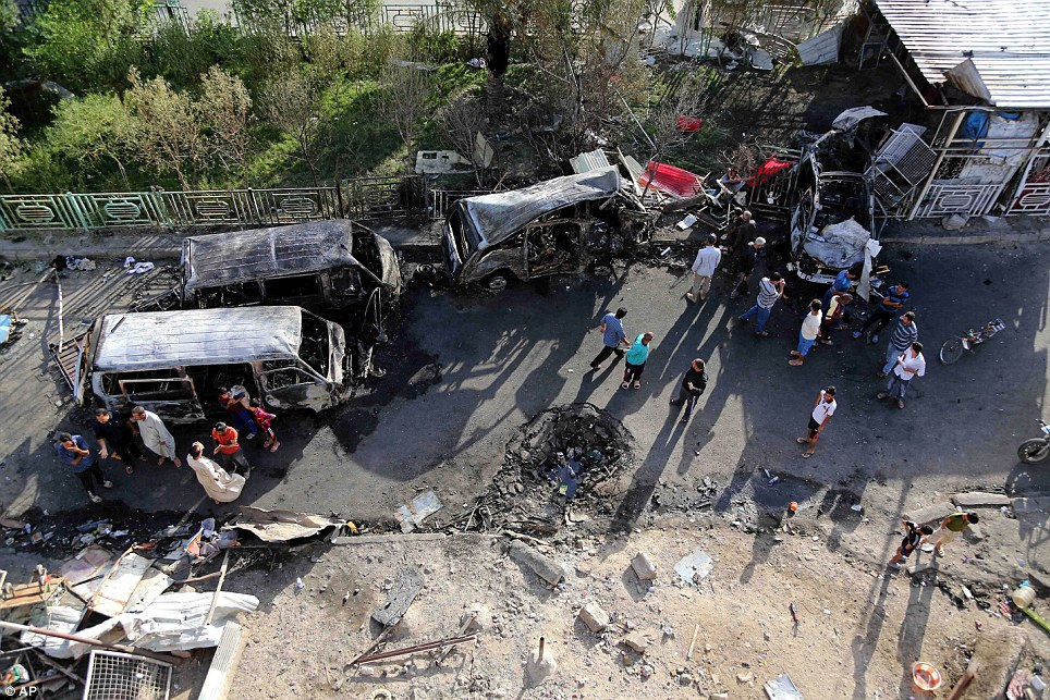 Terror blast: Iraqis inspect the site of a car bomb explosion in the Shi'ite Sadr City district of Baghdad which killed at least 12 people and wounded dozens more