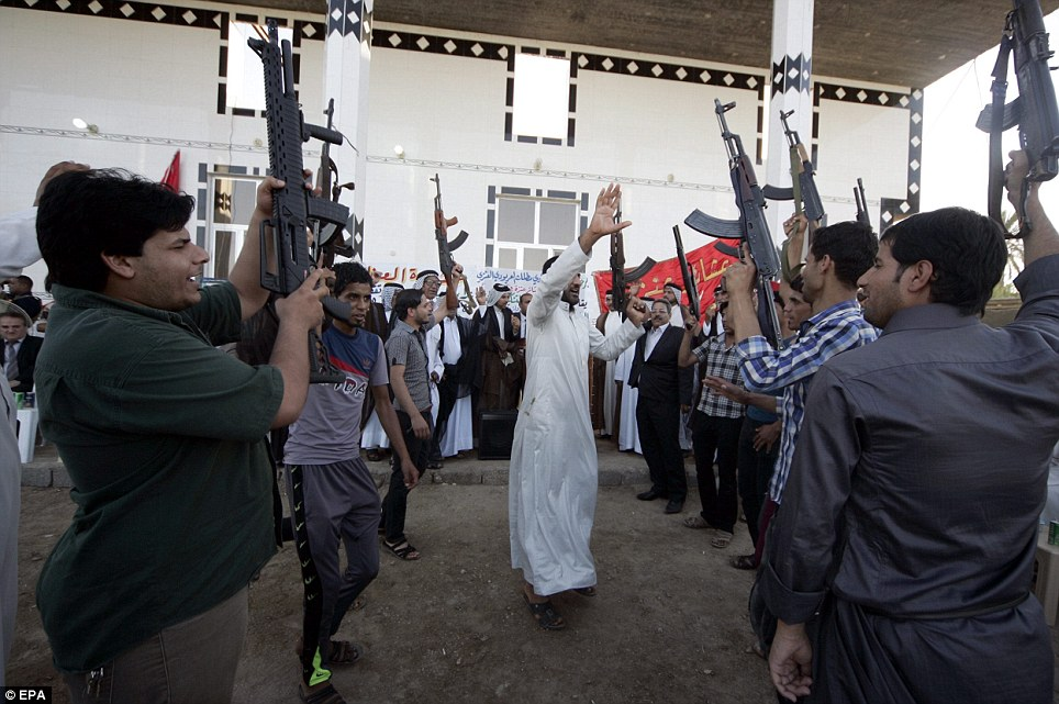 Ready for the fight: Iraqi Shi'ite volunteers who have joined forces with Iraqi troops against ISIS hold weapons and chant slogans in Karbala city