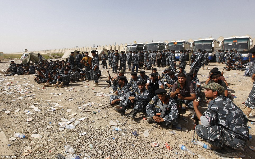 Mobilising troops: Shi'ite volunteers who have joined the Iraqi army to fight against Sunni militants gather with their weapons in Baghdad