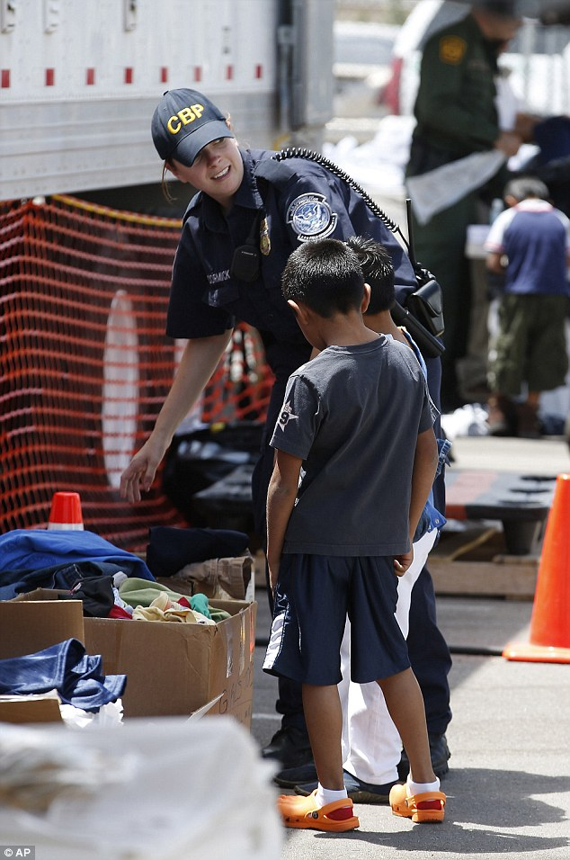 Caring: Two boys are helped to pick out clothing after arriving at a border placement center in Arizona