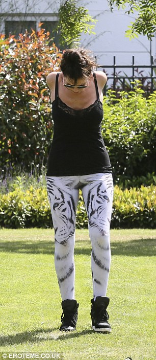 Stretch it out: She was happy to flaunt her slim physique in her white tiger print leggings which she teamed with black wedged trainers
