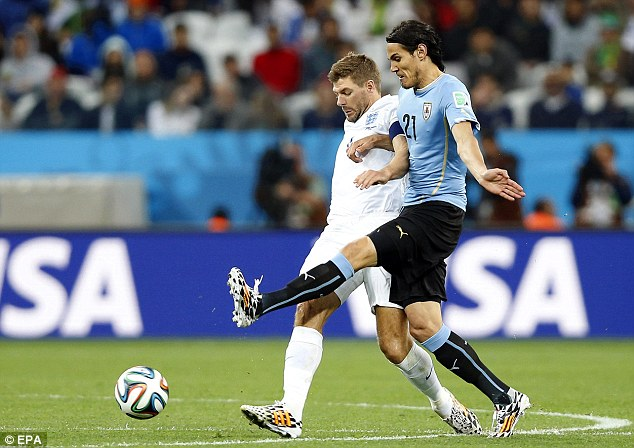 Holding on: Gerrard tussles with Edinson Cavani as England struggled to thwart Uruguay