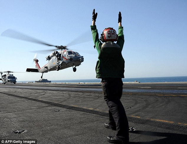MH-60R Sea Hawk helicopter lands on the aircraft carrier USS George H.W. Bush during flight operations in the Arabian Gulf on June 17, 2014