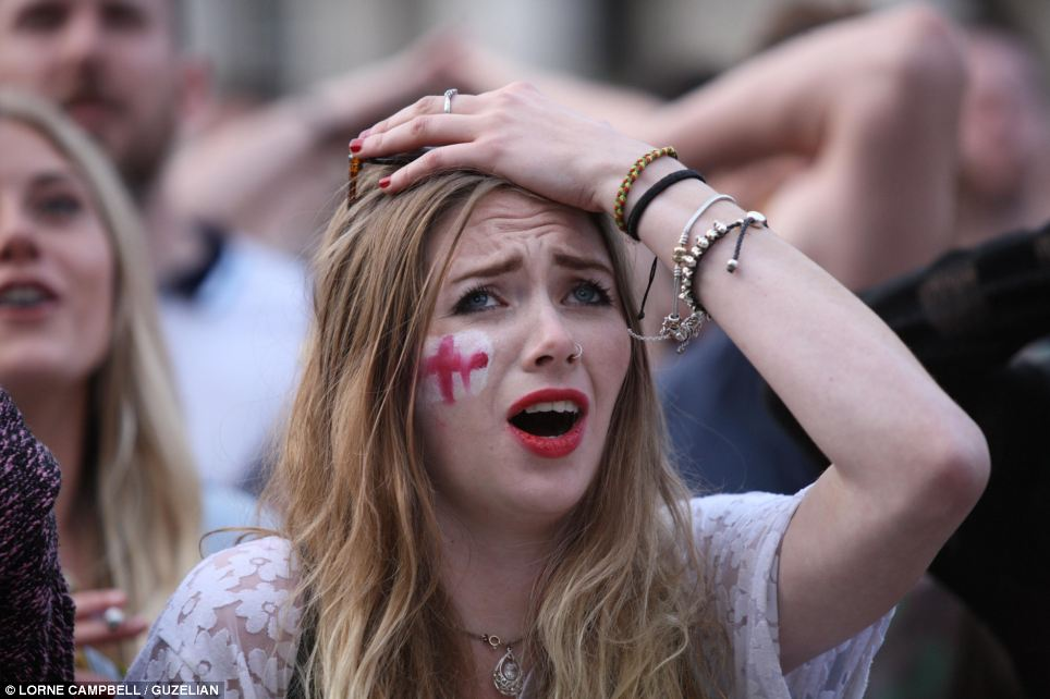 And at home, an England fan watches her team's match with Uruguay on the large outdoor screen in Millennium Square in Leeds, West Yorkshire