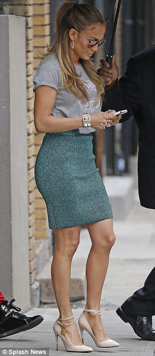 Chic combo: The I Luh Ya Papi star donned a skin-tight textured high waisted green skit that showed off her famous derriere with a loose fit grey T-shirt that had a giant pair of lips on front