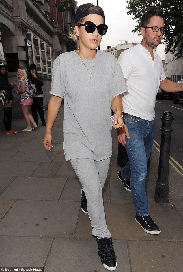 Busy bee: The star didn't even have time to change out of her slouchy grey tracksuit as she touched down in London