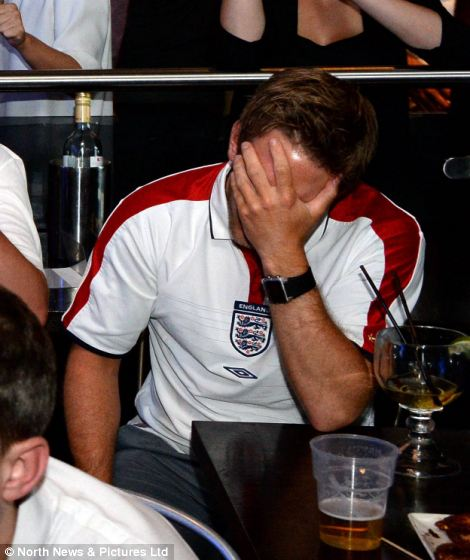 A fan in Shark Bar in Newcastle holds his head in this hands after Suarez put Uruguay ahead