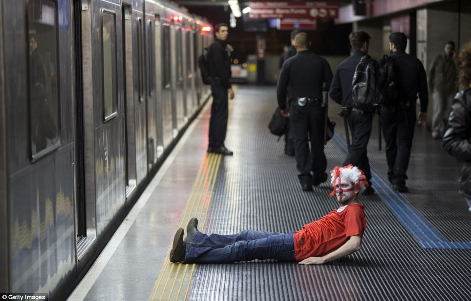 An England fan lies on the platform of Sao Paulo's Pedro II metro station after travelling to Brazil to see his team lose their first two group games to Italy and Uruguay