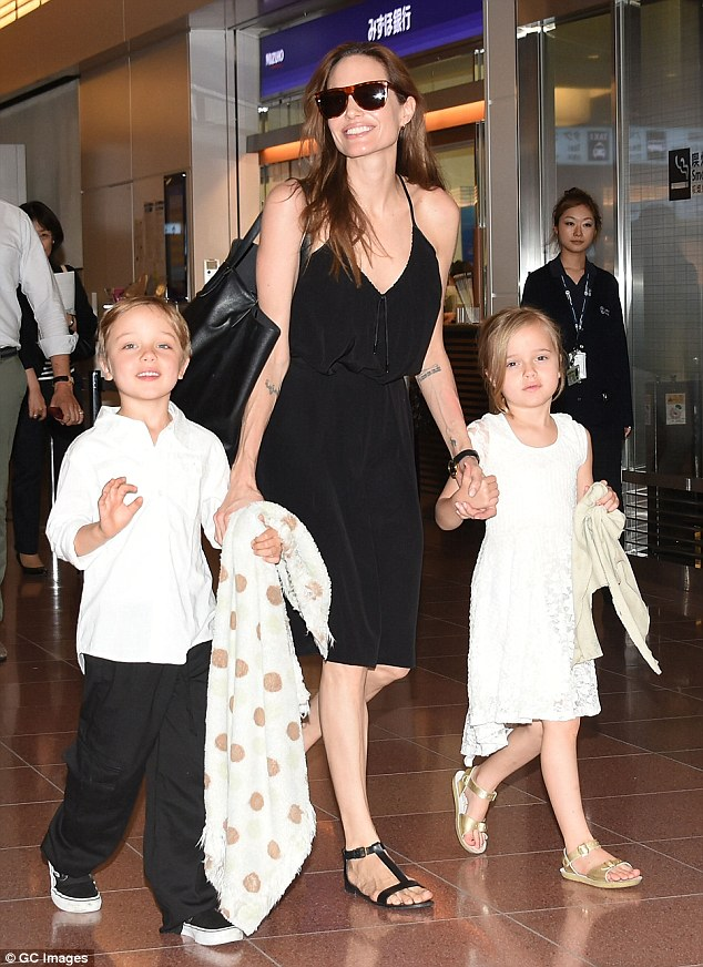 Maleficent herself: Angelina Jolie, seen here with six-year-old twins Knox and Vivienne, arrived at the airport in Tokyo on Saturday in a plunging black dress