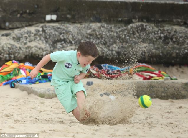 Kai Rooney doesn't let a bit of sand stop him from giving his all in this game of football