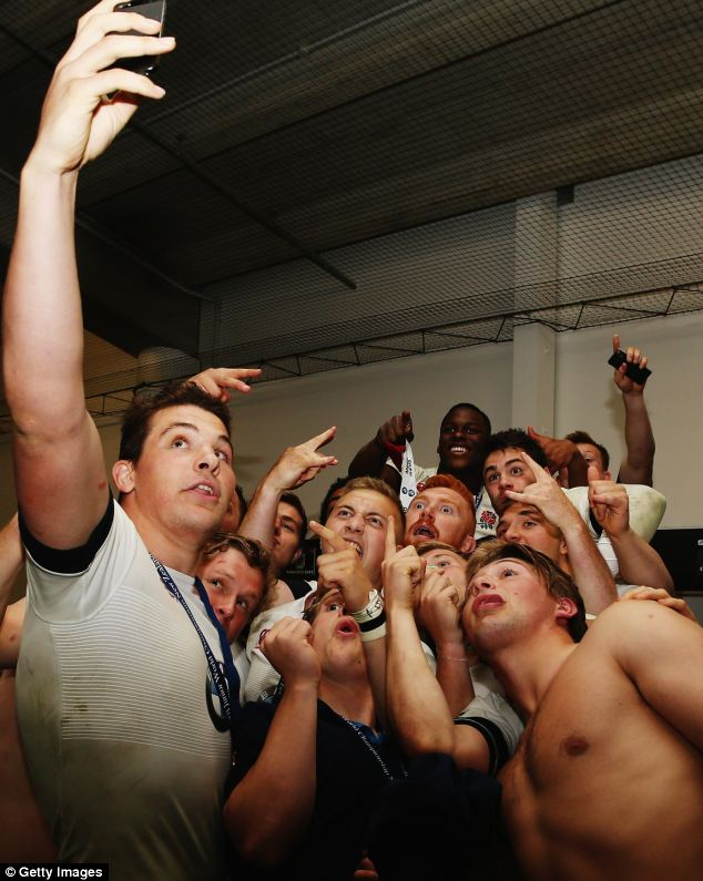 Celebration: England players take pictures in the dressing room retaining their title