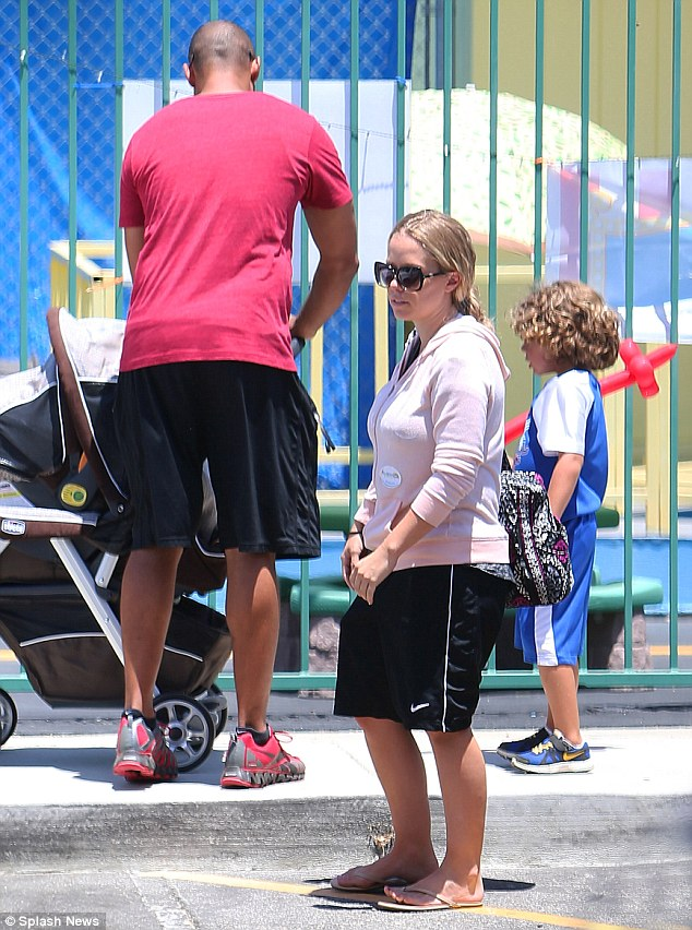 Looking unified: Hank tended to new baby Alijah as Kendra headed toward the car