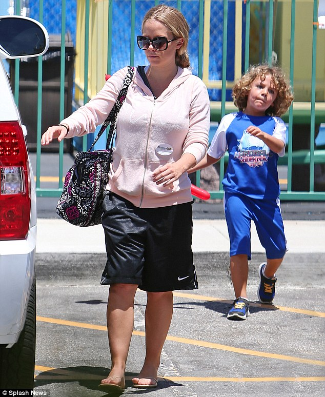 On mommy duty: The Playboy cover girl wore a pink hoodie with black Nike shorts; son Hank Jr trailed behind