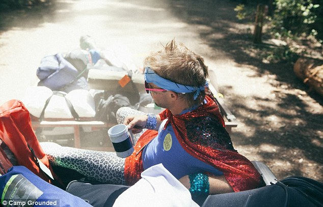 A Camp Grounded participant relaxes in what appears to be festive superhero attire