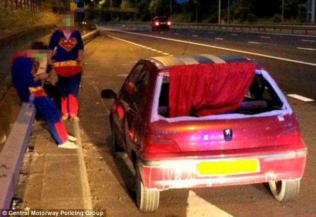 Caught: The two men, dressed in matching superman costumes, stand next to their customised car. Officers from the Central Motorway Policing Group stopped the vehicle on suspicion of driving without insurance