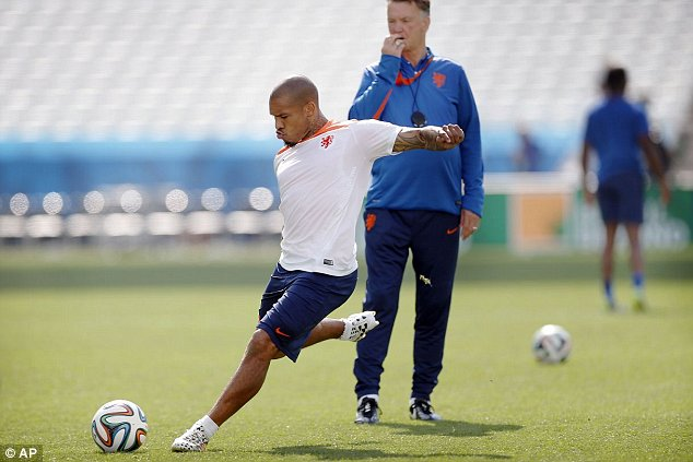 Nigel de Jong of the Netherlands kicks the ball while coach Louis van Gaal watches, during a training session at the Itaquerao Stadium in Sao Paulo, Brazil, Sunday, June 22, 2014.  The Netherlands will play Chile in a match that will decide the winner of Group B at the 2014 soccer World Cup. (AP Photo/Wong Maye-E)
