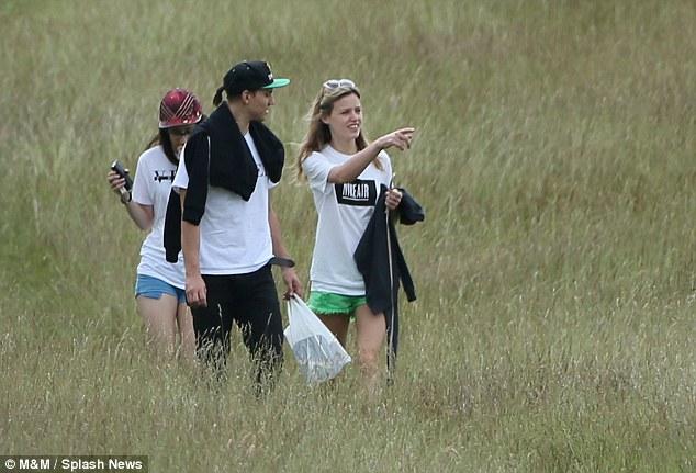 Nature walk: The trio were seen walking through long grass in a field