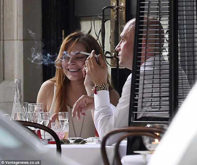 Taking a break: Lindsay and her friend were both spotted smoking cigarettes outside the Mayfair eatery