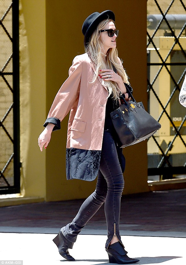 Sunny stroll: Ashlee finished her casual look off with a black pork-pie hat, a large handbag, and pointy wedge booties