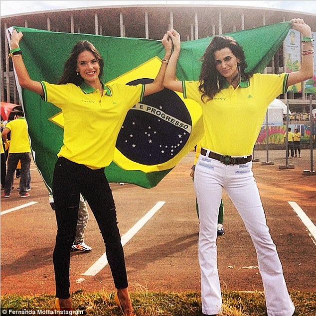Model fans: Alessandra Ambrosio, in Frame Denim jeans, and fellow beauty and host of Brazil's Next Top Model, Fernanda Motta, were at the Brazil versus Cameroon game on Monday