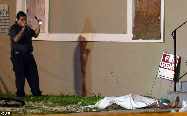 An investigator films an area of a scene where at least two people were killed and multiple others wounded following a shooting early on Tuesday in Miami's Liberty City neighborhood
