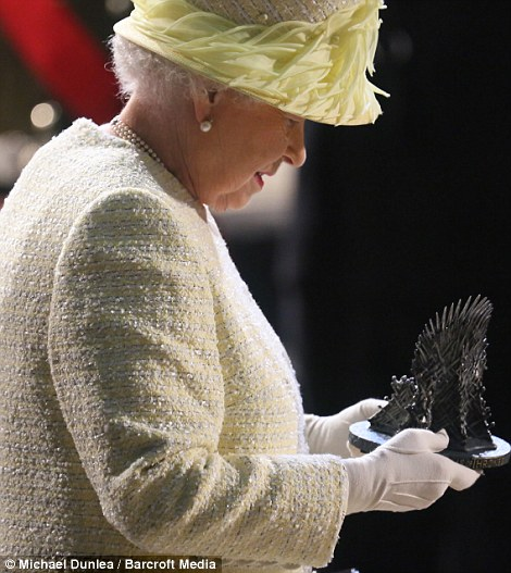 The Queen holds a miniature Iron Throne that seems slightly more manageable