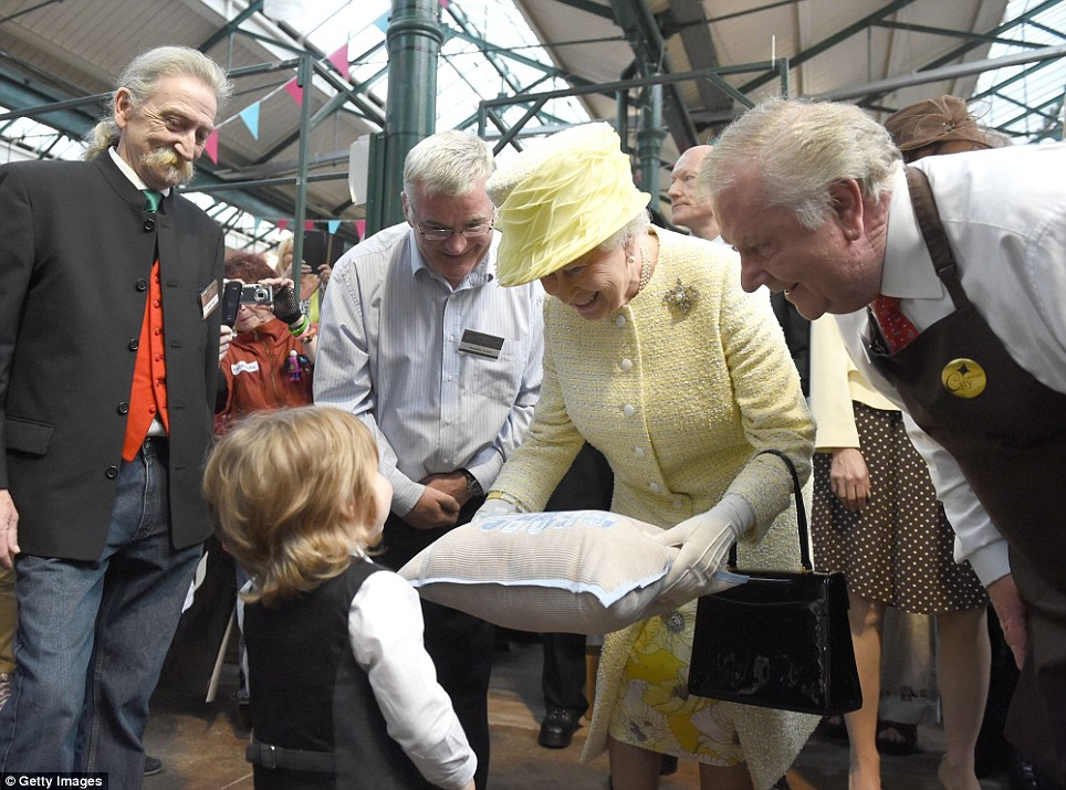 Adorable: The Queen looks delighted after being presented with a cushion by a tiny well-wisher during her visit to the lovely St George's covered market in Belfast