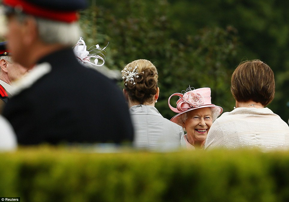 Enjoying the day: The Queen, who had changed into a pretty pale pink ensemble, beamed as she was introduced to guests at Hillsborough Castle