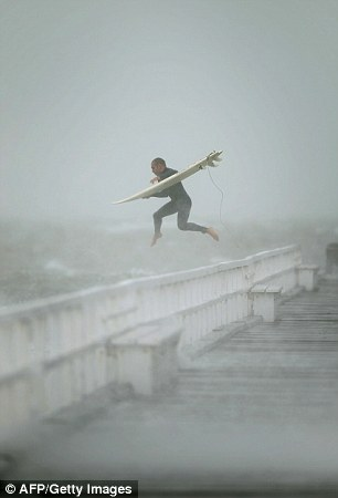 Jumping from the pier at the Melbourne beach a man takes the plunge despite the wild weather conditions