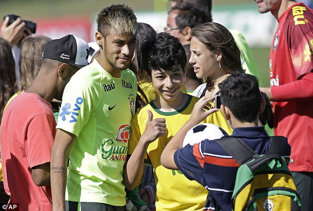 Smile: Neymar poses for a photograph with young fans prior to the training session. About 50 children who were victims of floods and landslides in Rio state back in 2011 watched the training