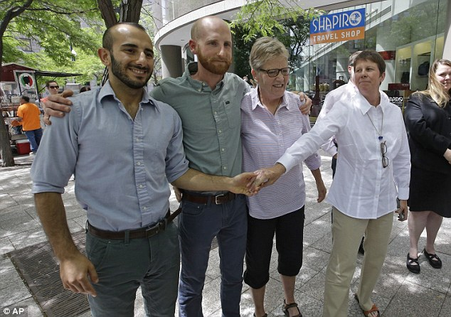 Celebrating in Utah: From left, plaintiffs Moudi Sbeity, Derek Kitchen, Laurie Wood and Kody Partridge, two of the three couples who brought the lawsuit against Utah's gay marriage ban, stand together at a news conference outside their lawyer's office in Salt Lake City