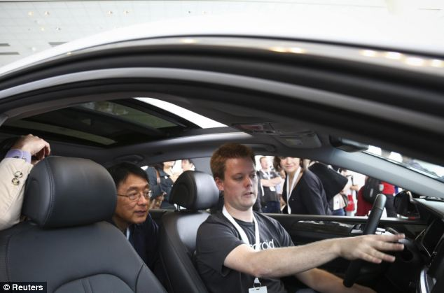 Google employee Michael Woodward (right) talks about the newly-announced Android Auto to conference attendees at the Google I/O developers conference