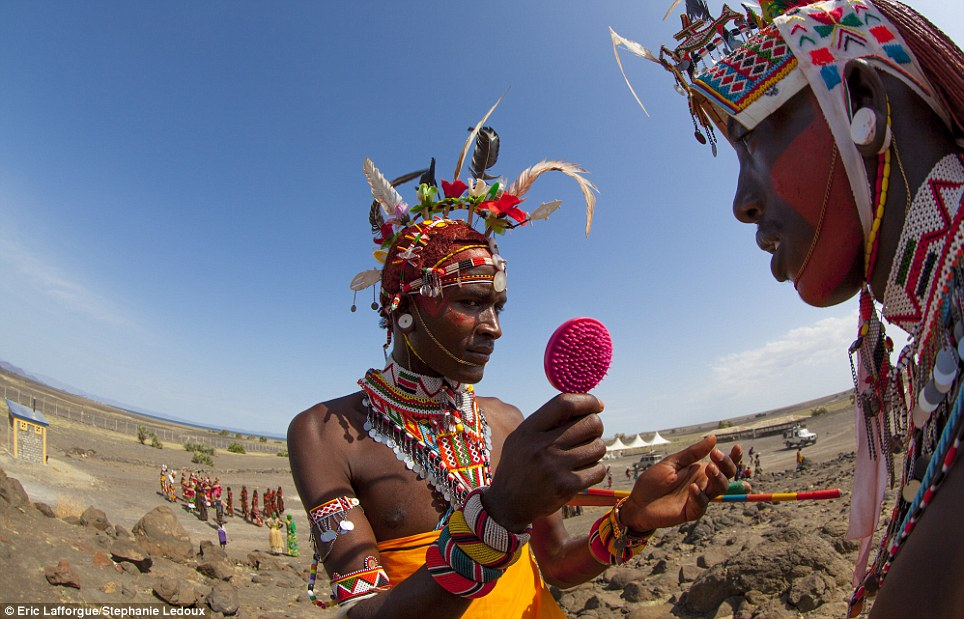 Looking good: A Samburu man checks his crimson make-up in an incongruous pink hand mirror, as he gets ready to participate in a traditional circumcision ritual