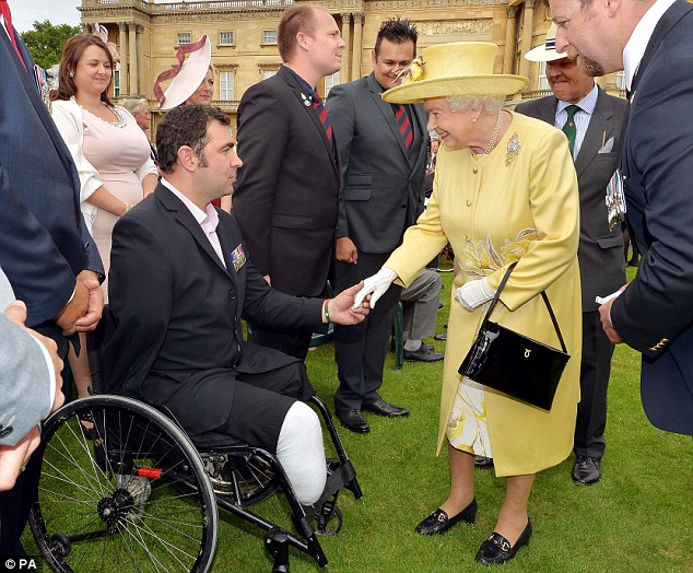 Servicemen: Queen Elizabeth talks to Andy Reid ex 3rd Battlion the Yorkshire Regiment, who lost both legs and an arm in Afghanistan in 2009 in an bomb attack