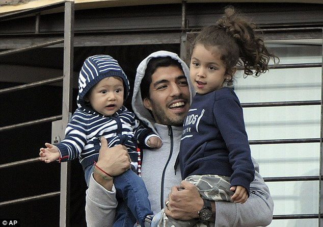 Banned: Uruguay and Liverpool striker Luis Suarez (pictured with his children) is banned from playing against Colombia