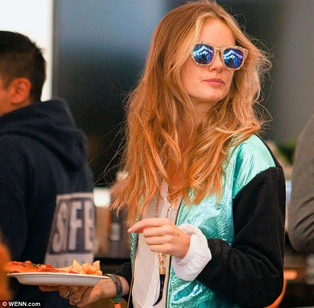 Cressida Bonas grabs a bite to eat from a festival snack bar at Glastonbury, where she has been spotted getting close to actor Will Poulter