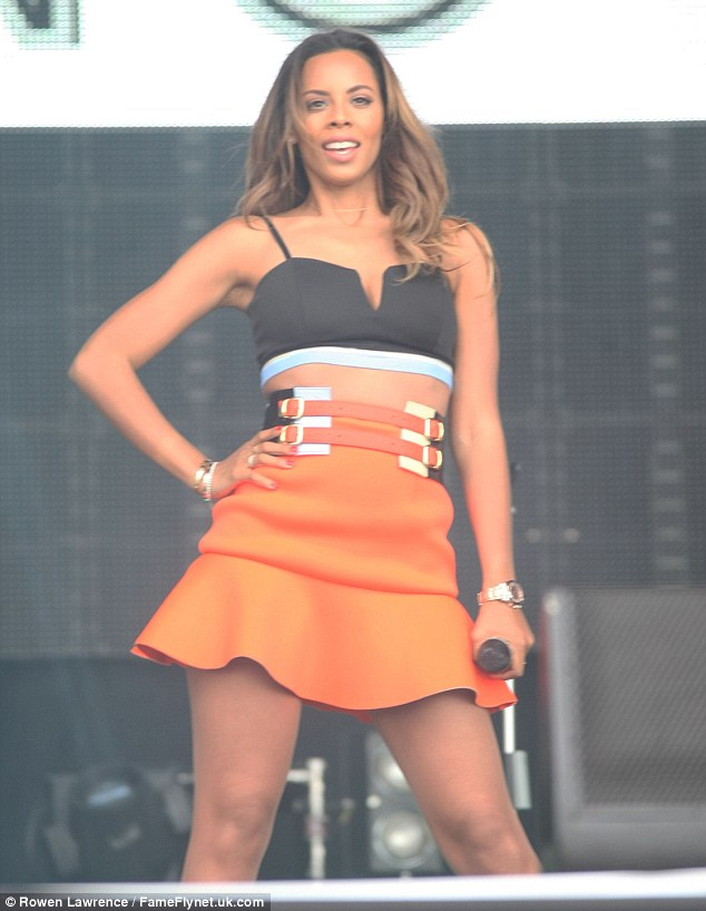 Summer style: Rochelle, 25, looked stunning in a black bralet which she teamed with vibrant orange mini skirt and a double waist belt