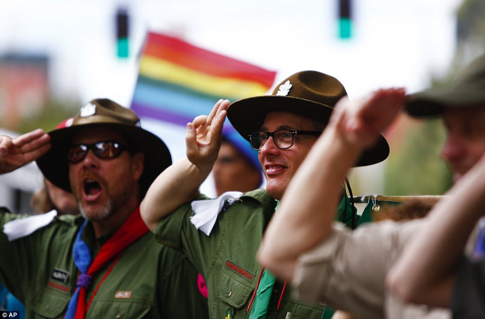 Scoutmasters for an inclusive scouts group salute parade participants in Seattle