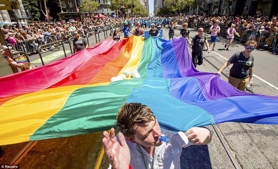 Marchers carry a rainbow flag down a street in San Francisco, California