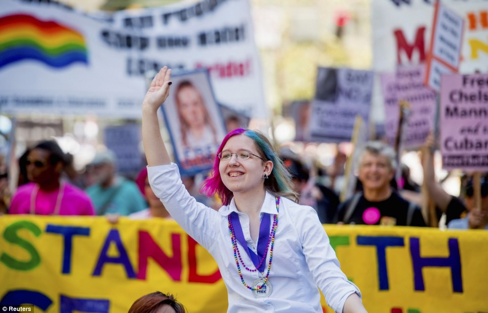 A woman waves as supporters of Chelsea Manning hoist signs in San Francisco
