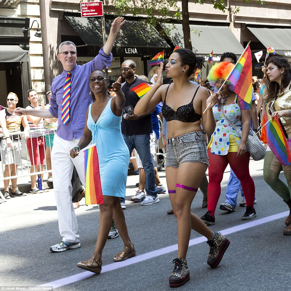 New York's first family: Chiara de Blasio (right) blows kisses to the crowd gathered to watch New York's annual Gay Pride parade on Sunday. She was joined by parents Bill de Blasio (left), current New York mayor, and mom Chirlane McCray (center)