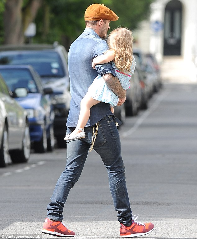 Hold on tight: Harper, who was wearing silver shoes, was seen with her arm around David's as he carried her