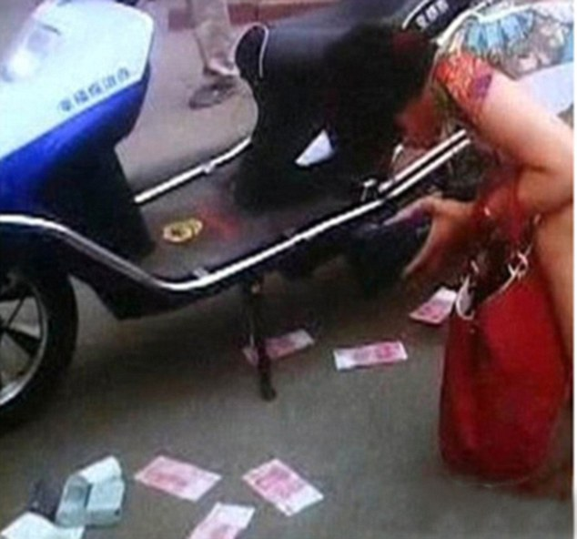 Furious after being fined, the woman slapped the RMB notes on the traffic policeman's motorcycle