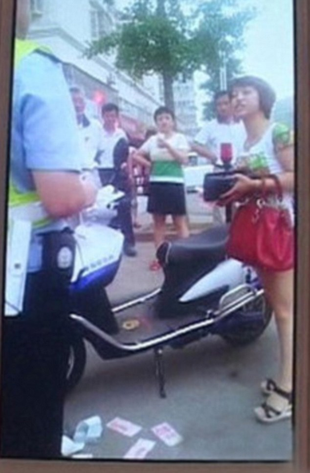"""A woman described as """"rich and arrogant"""" is facing jail in China for throwing money at a police officer. The woman struck in Nanjing City in Jiangsu Province in the east of China after being fined for illegally parking her car. Furious  after being fined, the woman slapped the RMB notes on the traffic policemanís motorcycle.  Then she threw them to the ground in a bid to get him to humiliate himself into picking them up. Bystanders were so angry that someone called for police reinforcements after she also threw the money into the face of the officer, and seemed to be hitting him with wads of cash. Reinforcements came and showed less restraint than their colleague, arresting her and taking the woman to a police station for further investigation. Cho Lein Peng, an eyewitness, said: """"The woman seemed crazed because of this trifling fine.  She was throwing her weight around, then smashed the money on his bike, then slapped his face with it. She told him 'I spend more in a single trip to th"""