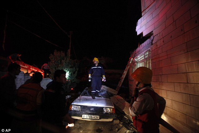 Taking control: Fire fighters and a crowd of Palestinians inspect the blown-up house of Amer Abu Aisheh - one of two Palestinians identified by Israel as suspects in the killing of three Israeli teenagers